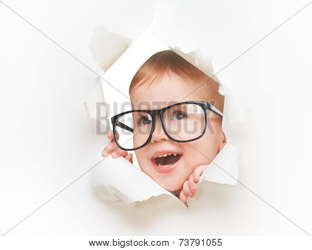Funny  Child Baby Girl With Glasses Peeping Through Hole In An Empty White  Paper