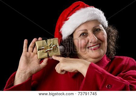 Happy Old Woman With Red Cap Points At Xmas Gift.
