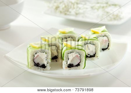 Cucumber Maki Sushi  - Roll made of Crab Meat, Cream Cheese and Black Tobiko inside. Cucumber outside. Topped with Lemon Slice