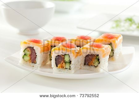 Maki Sushi made of Tuna and Cucumber inside. Topped with Salmon and Tuna