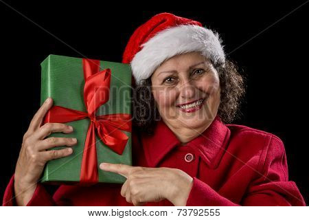 Happy Female Pensioner Pointing At Wrapped Gift.