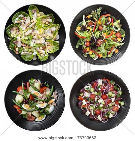 Set of different salads on white background.  Includes chicken Caesar, garden, Nicoise, and Greek.
