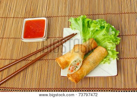 Fried Spring Rolls, One Cut, On A Plate With Chopsticks