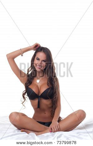 Smiling slim girl posing sitting on bed in studio