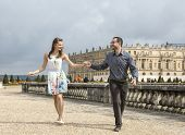 picture of versaille  - Happy young couple holding hands run to the camera in the garden of the Palace of Versailles in France - JPG