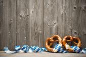 stock photo of pretzels  - Bavarian pretzels with ribbon on wooden board - JPG