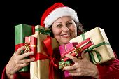 picture of gold tooth  - Smiling aged lady with sparkling eyes is embracing eight unicolored wrapped Christmas presents - JPG