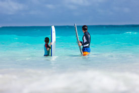 stock photo of boogie board  - Father and son in ocean with boogie boards waiting for a wave - JPG