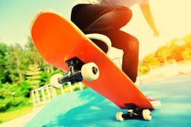 stock photo of skateboard  - young woman skateboarder legs skateboarding at skatepark - JPG