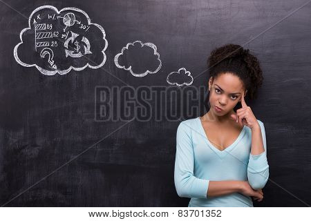 Dissatisfied afro-american woman trying to solve a problem on chalkboard