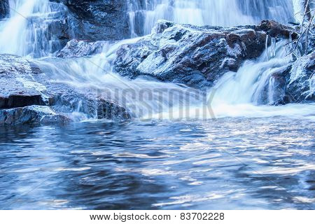 Waterfall and frozen log