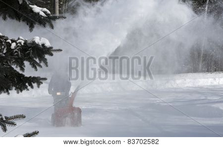Man cleaning snow with blowing machine