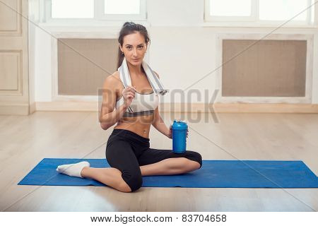 Beautiful athletic sporty woman sitting on yoga mat after some exercises with blue shaker in her han