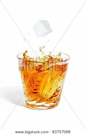 Ice Cube Falls With Splashes Into The Glass With Alcohol