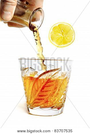 Alcohol Pours With Splashes Into The Glass With Slice Of Lemon