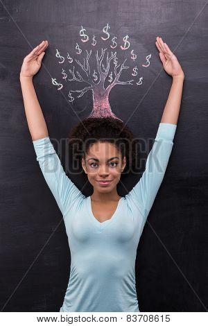 Afro-american woman near dollar tree painted on chalkboard