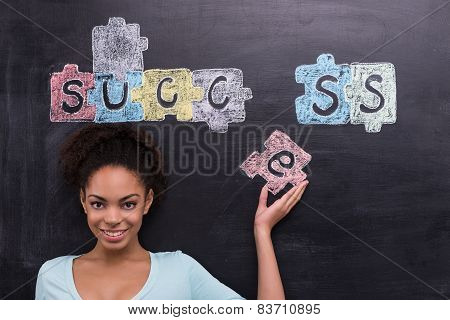 Young afro-american woman with painted puzzles on chalkboard