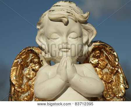 Praying Little Angel Figure With Golden Wings Isolated On Sky