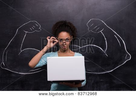 Afro-american woman with laptop and painted muscular arms on chalkboard