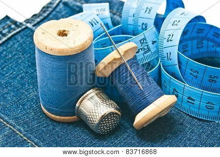 Thimble, Meter And Spools Of Thread On Denim