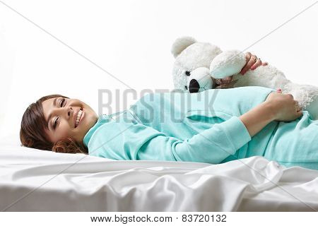 Merry expectant mother posing in embrace with toy