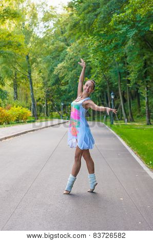 Girl dancer stands on tiptoes, ballet pirouette. Outdoors, spring