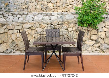 Rattan Table And Chairs In Cafe Against Stone Wall