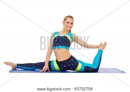 Smiling flexible girl doing gymnastic split