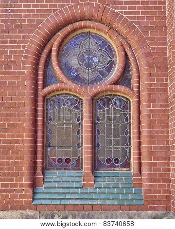 church window and red brick wall