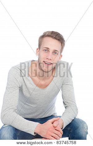Sympathetic Smiling Young Man On A Chair