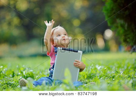 Child playing with tablet outdoors
