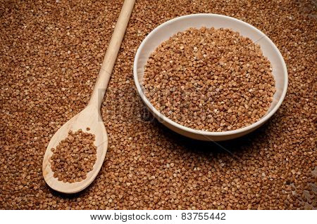 Buckwheat Groats On Wooden Spoon Next To Bowl