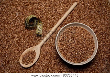Buckwheat Groats On Wooden Spoon Next To Bowl And Centimeter
