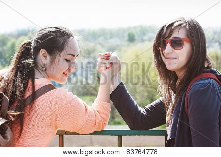 Girls engaged in arm wrestling
