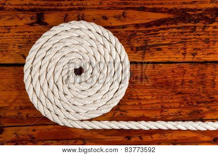 White Rope Coiled On Textured Wood