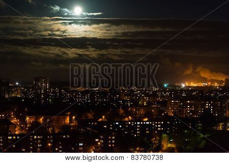 Full moon rising over night skyline of city