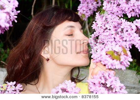 Woman Sniffs Redbud Flowers