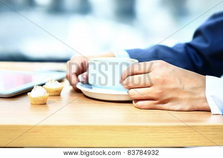 Businesswoman with tablet computer reading news at morning in cafe shop