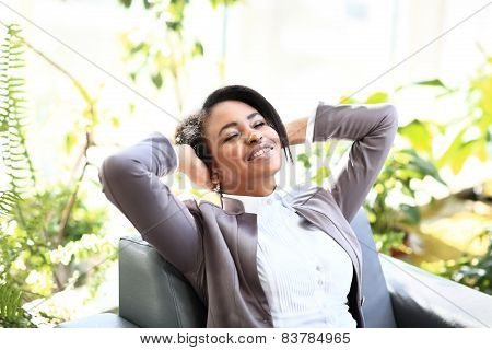 Portrait of a relaxed young businesswoman sitting in a bright office