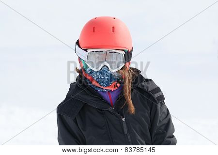 Girl Skier Portrait Wrapped Up Warm In Skiing Gear With Orange Helmet And Goggles