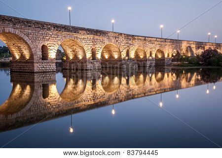 night view of Merida Roman bridge over the river Guadiana with reflections on water