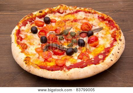 Pizza with anchovies and olives on wood