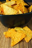 foto of nachos  - Nacho cheese flavored tortilla chips in a dark bowl on a wooden table.