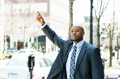 foto of waving hands  - An African American business man raises his hand to hail a cab in the city - JPG