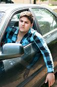 pic of irritated  - An irritated young man driving a vehicle with his head and arm hanging out of the window - JPG