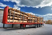 stock photo of logging truck  - Trucks charged with wood logs waiting for delivery - JPG