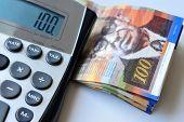 stock photo of shekel  - Calculator with one hundred New Israeli Shekel notes isolated on white - JPG