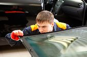 stock photo of auto repair shop  - Real Mechanics checking the new windshield of black car in Auto Repair Shop - JPG