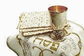 image of hebrew  - the symbols of the feast of Passover three pieces of matzah glass white cloth with embroidery and font on the Hebrew Pesach on a white background isolated - JPG