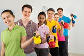stock photo of kettling  - Multiethnic Group Of People Standing In Row Holding Kettle Bell Over White Background - JPG